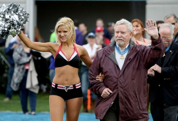Medal of Honor Recipient Donald Ballard is escorted onto the field by a member of the Atlanta Falcons cheerleaders during the 2014 Medal of Honor Bowl. (Paul Zoeller/Staff)